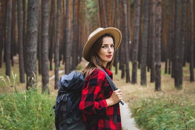 Молодая женщина в шляпе, красной рубашке и рюкзаке в лесу. поход в лес.