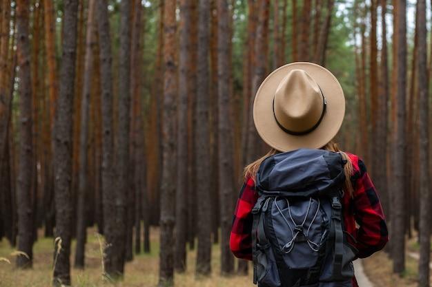 松林の中の帽子、赤いシャツ、バックパックの若い女性。森の中でのキャンプ。