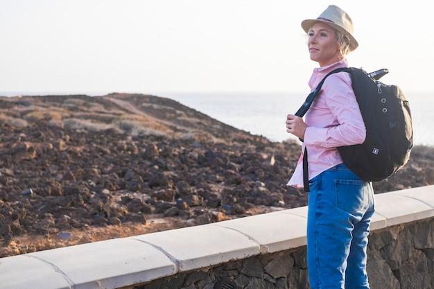 海と空に対してビーチの近くのバックパックと堤防の横に立っている帽子をかぶった若い女性。ビーチの近くに立って、景色を楽しみながら笑顔の帽子をかぶった幸せな白人女性。