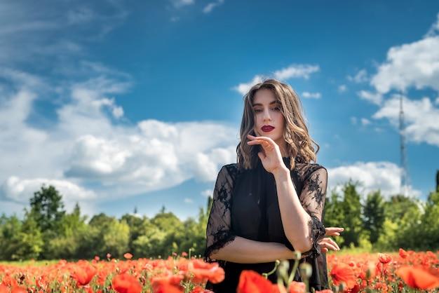 양 귀 비 필드에서 모자 도보에 젊은 여자는 꽃을 선택합니다. 여름 시간
