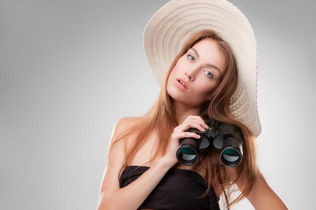 Молодая женщина в шляпе с биноклем