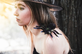 Young woman in hat with decorative spider on shoulder looking away