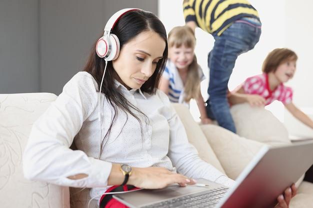 헤드폰을 끼고 노트북을 들고 소파에 앉아 아이들을 놀고 있는 젊은 여성. covid19 전염병 개념 동안 재택 근무의 도전
