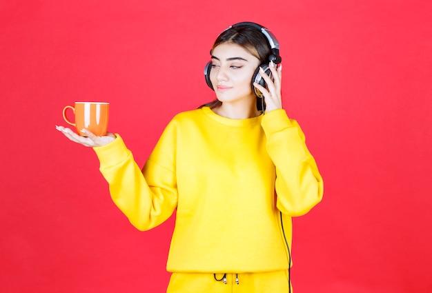 赤い壁にお茶を持ってヘッドフォンで若い女性