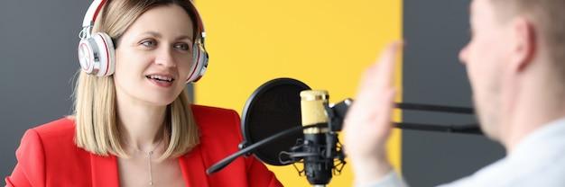 라디오 방송국에서 남자를 인터뷰하는 헤드폰을 끼고 라디오 호스트 개념으로 일하는 젊은 여성