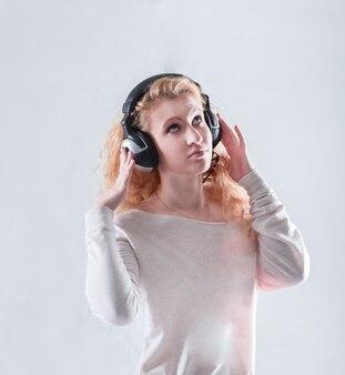 Молодая женщина в наушниках, слушающая музыку