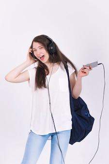 Молодая женщина в наушниках поет песни на белой стене