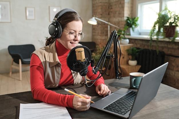 헤드폰을 끼고 노트북 작업을 하고 마이크에서 말하는 팟캐스트를 녹음하는 테이블에 앉아 있는 젊은 여성