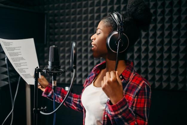 オーディオレコーディングスタジオでヘッドフォンの歌の若い女性。