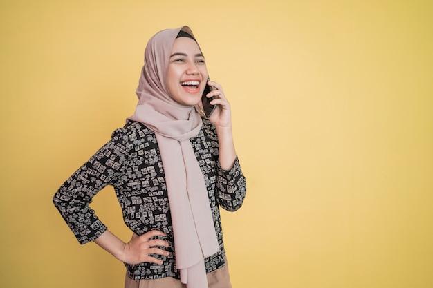 머리 스카프를 두른 젊은 여성이 활짝 웃고 행복한 전화를 받는 동안 허리에 손을 편안하게 ...