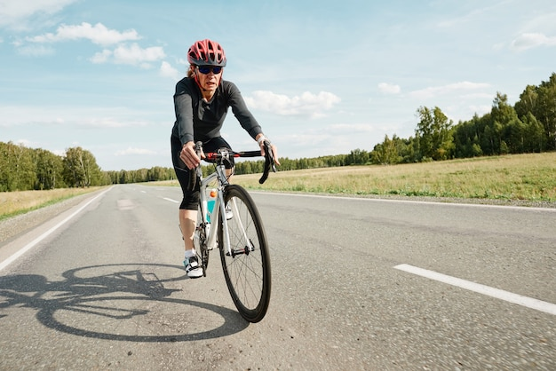 헬멧을 쓴 젊은 여성이 자전거에 앉아 야외에서 자전거 도로를 타고 있다