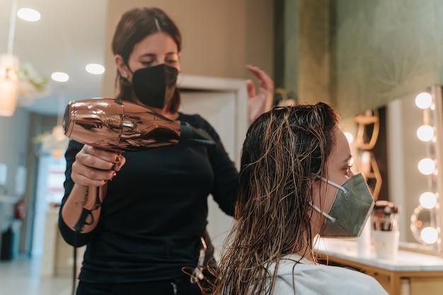 미용실에서 20 대 젊은 여성의 머리카락을 말리는 30 대 젊은 여성. 수평