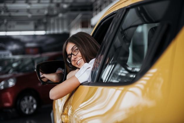 Молодая женщина в ее новой машине улыбается