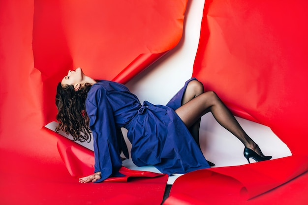 높은 뒤꿈치 신발, 나일론 스타킹, 찢어진 빨간 종이 배경에 보라색 비옷에 젊은 여자