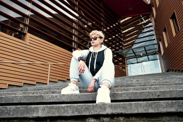 도시 계단에 앉아 운동복과 선글라스를 착용하는 힙합 스타일의 젊은 여자