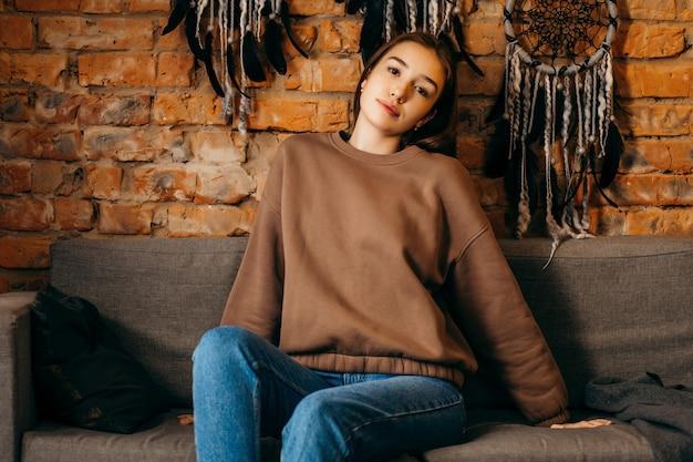 Молодая женщина в толстовке с капюшоном позирует в студии на пространстве кирпичной стены