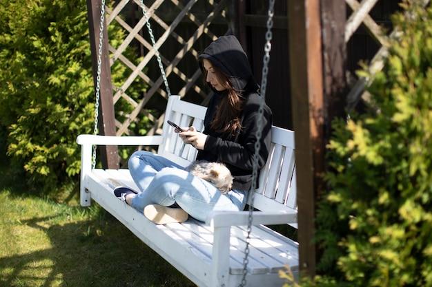 Молодая женщина в толстовке с капюшоном сидит на деревянных качелях на заднем дворе, смотрит вебинар, болтает онлайн в социальных сетях