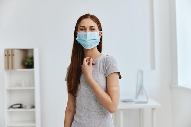 彼女の肩の安全に殺菌パッチが付いている医療マスクを身に着けている病院の若い女性