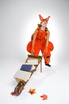 Молодая женщина в образе белки с тележкой и книгами