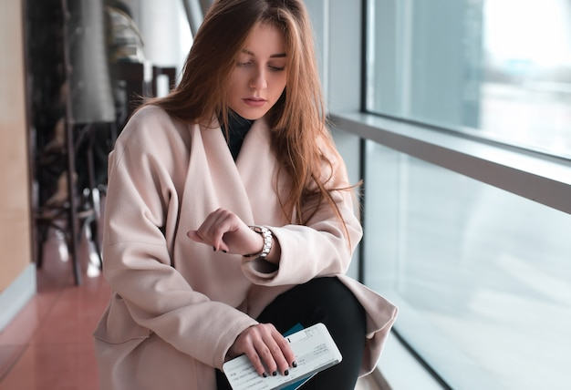 国際空港で若い女性がフライトを待っており、腕時計をチェックし、動揺したり心配したりしている。到着、欠航、キャンセル、遅延のフライトのコンセプト。