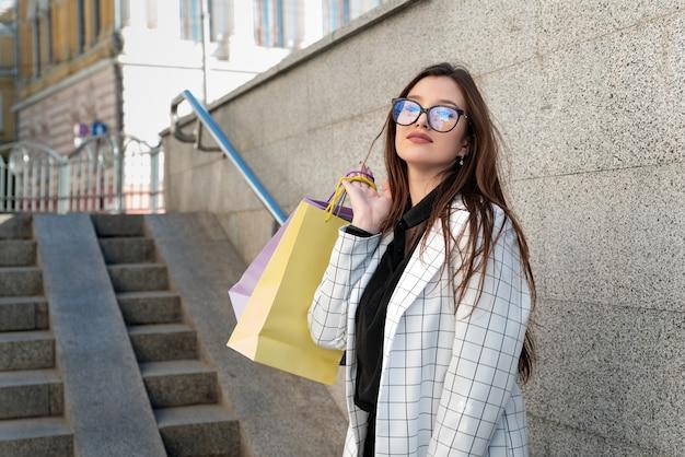 자 켓과 멀티 컬러 종이 봉투와 안경에 젊은 여자. 쇼핑 후 학생.