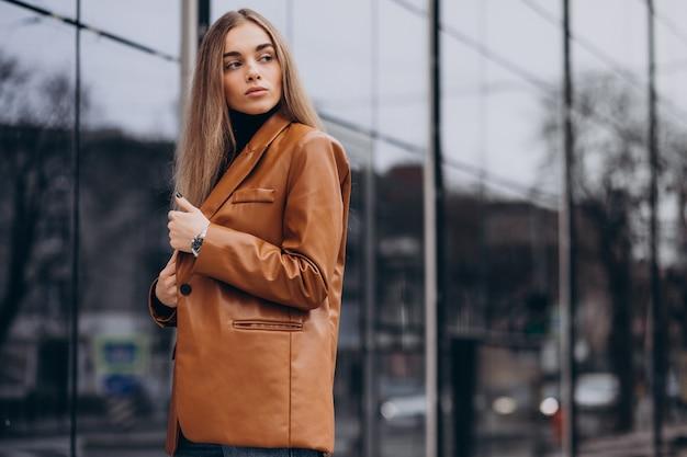 Молодая женщина в куртке гуляет по городу
