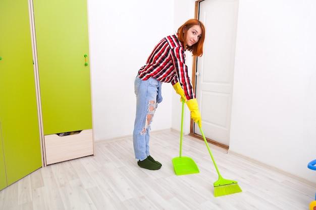 녹색 빗자루와 삽으로 바닥을 쓸고 청바지와 격자 무늬 셔츠에 젊은 여자