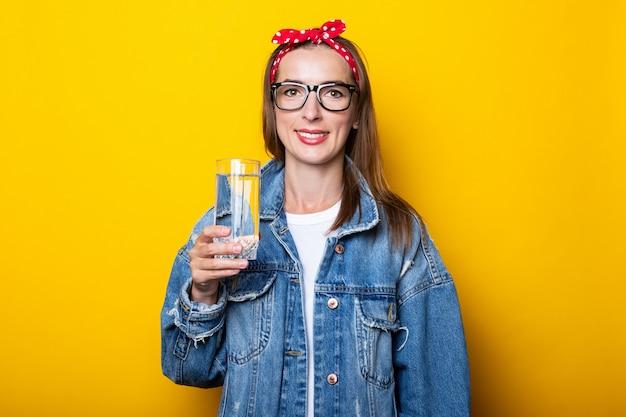 ジーンズ、メガネ、きれいな水のガラスを保持しているヘッドバンドの若い女性