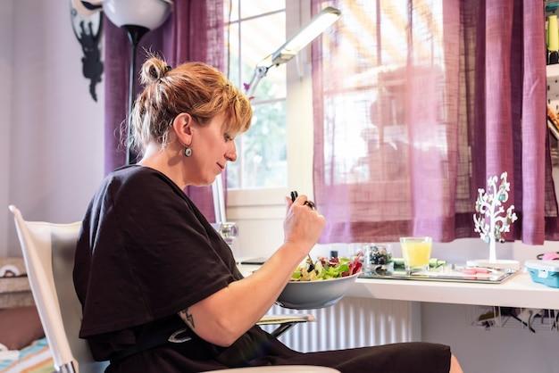 Молодая женщина в ювелирной мастерской делает перерыв во время еды веганского салата