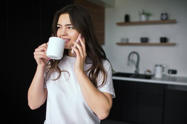 調理中にキッチンで若い女性。電話で話し、白いカップのお茶やコーヒーを飲みます。オンライン会話ワイヤレス。現代の技術とデバイス。