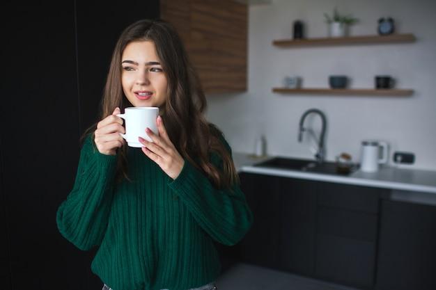 Молодая женщина на кухне во время карантина. девушка в зеленый свитер пить чай или кофе из белой чашки и смотреть в сторону. одни на кухне.