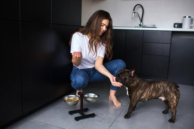 Молодая женщина на кухне во время карантина. девушка сидеть в приседе и кормить французского бульдога. взрослый питомец ест собачью еду. уход за животными.