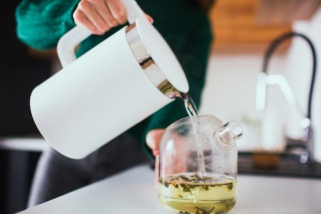 Молодая женщина на кухне во время карантина. рука держать белый электрический умный чайник и налить горячую воду в чайник. приготовление чая на обед или ужин.
