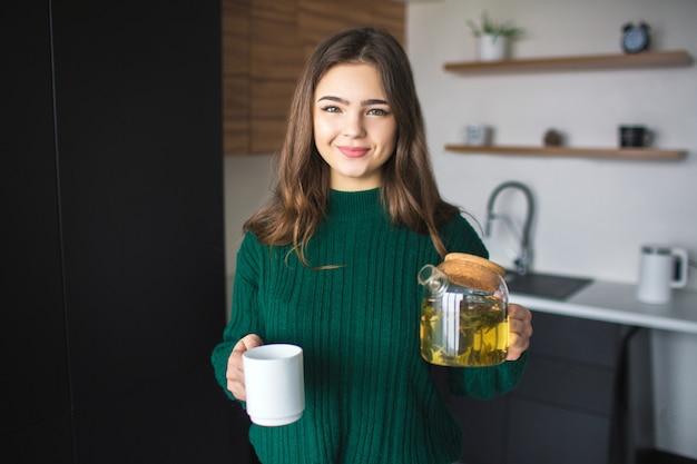 検疫中にキッチンの若い女性。陽気な陽気な女の子はティーポットと白いカップを保持します。笑顔でカメラにポーズします。
