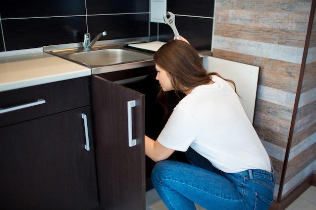 キッチンで若い女性。シンクの下に漏れているパイプを修正する女性の人。レンチを手に持ってください。一人でキッチンの固定。