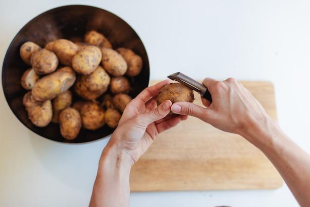 Молодая женщина на кухне в фартуке, чистка картофеля