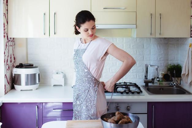 キッチンで若い女性は彼女の背中にエプロンを結び目
