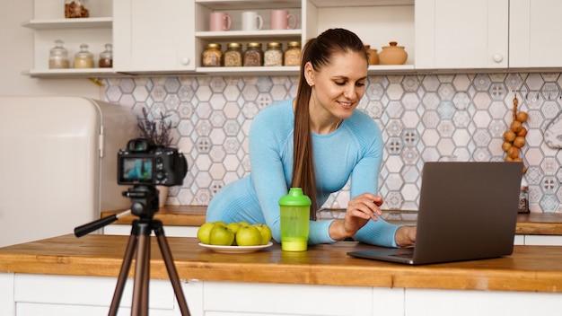 노트북 미소와 함께 부엌에서 젊은 여자. 음식 블로거 개념. 한 여성이 건강한 식습관에 대한 비디오를 녹화하고 있습니다. 삼각대에 카메라.