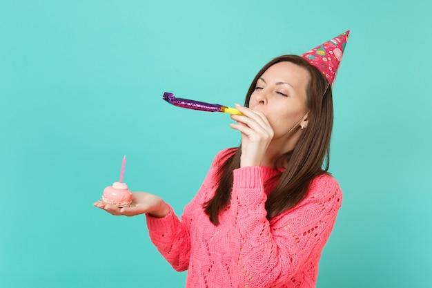 분홍색 스웨터를 입은 젊은 여성, 파란색 벽 배경에 격리된 채 눈을 감고 촛불을 들고 손으로 케이크를 들고 파이프를 연주하는 생일 모자를 쓴 젊은 여성. 사람들이 라이프 스타일 개념입니다. 복사 공간을 비웃습니다.