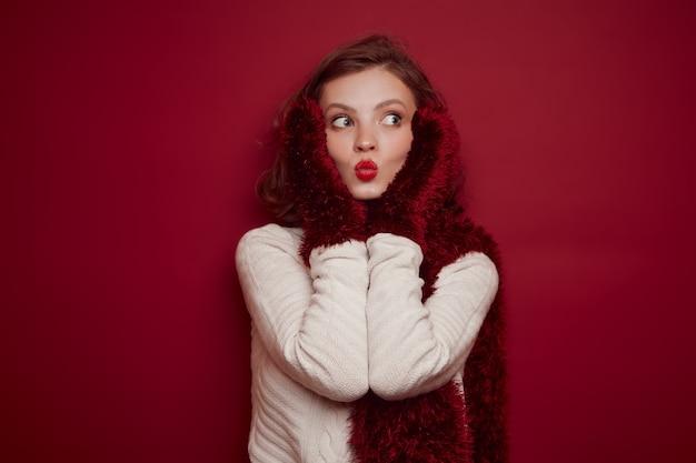 ニットセーターの若い女性はキスを送信します