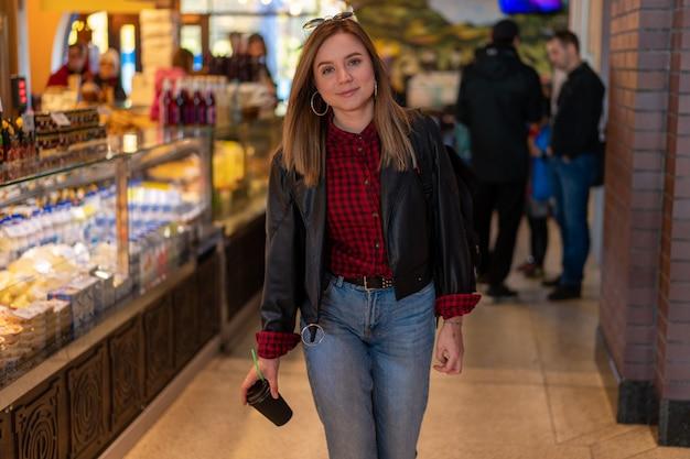 市場での革のジャケットの若い女性