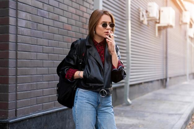 路上喫煙レザージャケットの若い女性
