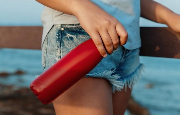 Молодая женщина в голубой футболке, держа в руке красную многоразовую бутылку с водой, крупным планом, обрезанный снимок. бутылка и макет футболки