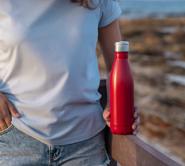 Молодая женщина в голубой футболке, держа в руке красную бутылку с водой, крупным планом, обрезанный снимок. бутылка и макет футболки