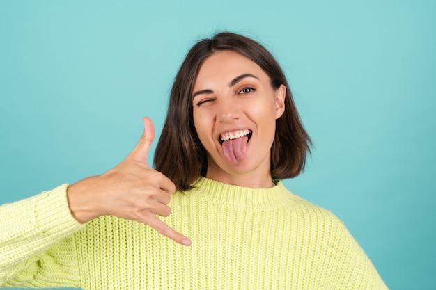밝은 녹색 스웨터 웃는 젊은 여자는 전화 제스처를 보여줍니다