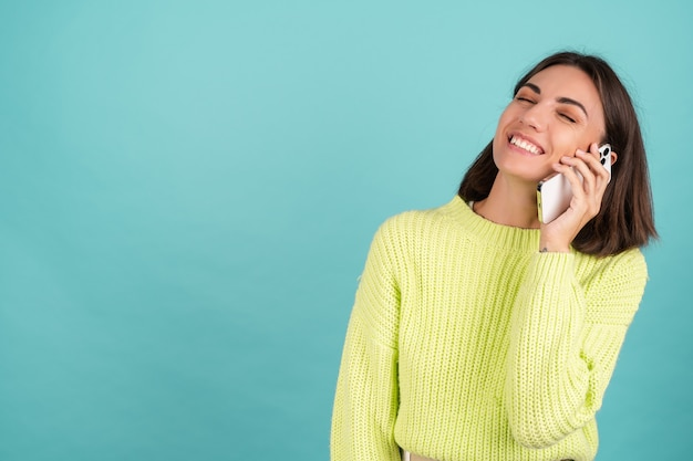 밝은 녹색 스웨터를 입은 젊은 여성, 휴대전화로 음성 메시지를 들으며 대화