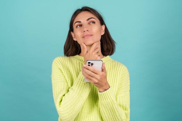 밝은 녹색 스웨터를 입은 젊은 여성, 휴대전화로 사려깊고 턱을 만지고