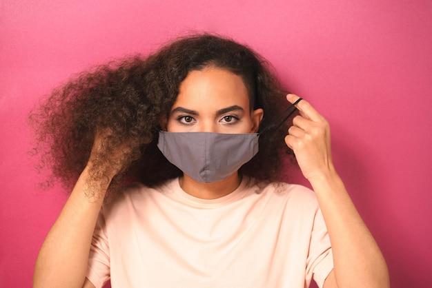 분홍색 벽에 고립 된 코로나 covid-19 및 sars cov 2 감염으로부터 다른 사람을 방지하기 위해 밝은 복숭아 색 티셔츠를 입은 젊은 여성