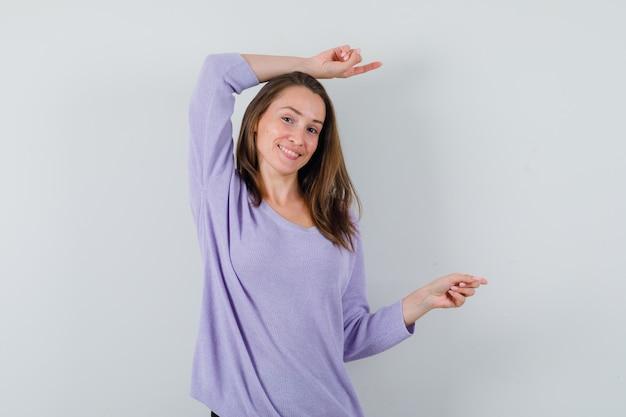 Молодая женщина в сиреневой блузке указывает в сторону над головой и радостно смотрит