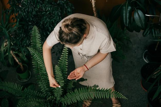 リネンの服を着た若い女性が、生産事務所ビルで花の世話をしています。上面図